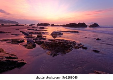 Sunrise scenery of a beautiful rocky beach in northern Taiwan, with golden sunlight rays from distant horizon reflected in the peaceful sea water under dramatic dawning sky ( Long Exposure Effect )