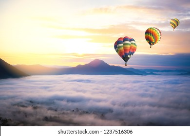 Sunrise scenery gold sky with hot air balloon flying over valley hill mountain and sea fog morning day in The north part of Thailand.