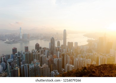 Sunrise scenery of Hong Kong, viewed from top of Victoria Peak, with a city skyline of crowded skyscrapers by Victoria Harbor & in Kowloon Downtown across the seaport~Cityscape of Hongkong in twilight