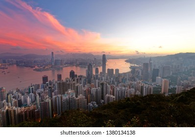 Sunrise scenery of Hong Kong, viewed from top of Victoria Peak, with a city skyline of crowded skyscrapers by the Harbour & Kowloon Downtown across the seaport under dramatic dawning sky