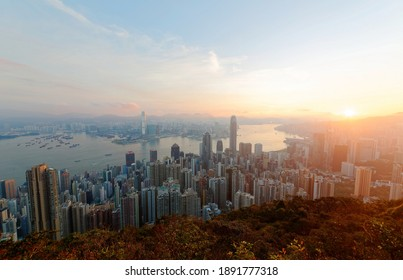 Sunrise scenery of Hong Kong, viewed from top of Victoria Peak, with a city skyline of crowded skyscrapers by Victoria Harbor and Kowloon Downtown across the seaport~ Cityscape of Hongkong in twilight