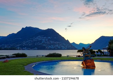Sunrise scenery of Lake Lugano, with a beautiful statue in the middle of a pool by lakeside & silhouettes of alpine mountains under dramatic dawning sky in background, in Paradiso, Lugano, Switzerland