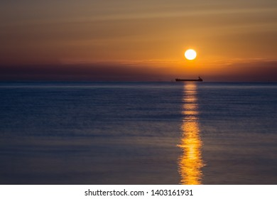 Sunrise at the sea with tanker ship silhouette in the background waiting for entering the port.