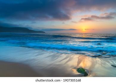 Sunrise seascape with haze and soft clouds at Killcare Beach on the Central Coast, NSW, Australia.