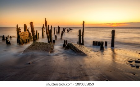 Sunrise seascape, light hits old wooden posts on the beach at Spurn Point Nature Reserve near Hull, Yorkshire, UK.