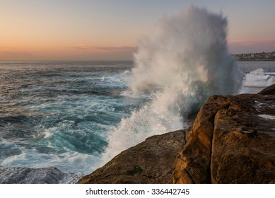 Sunrise seascape with unrest sea and blue water and with sky lit orange rocks and big crashing wave