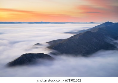 Sunrise as seen atop Boroka Lookout in the Grampians National Park in Victoria, Australia. A large amount of fog had rolled in before dawn and the sunrise illuminated the amazing landscape below.