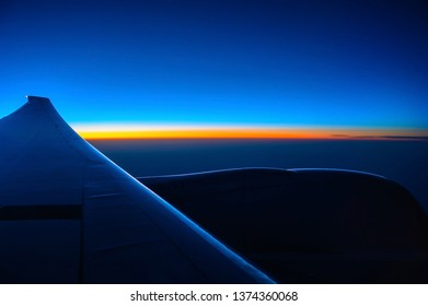 Sunrise seen from a commercial passenger jet airplane with the wing and engine in silhouette