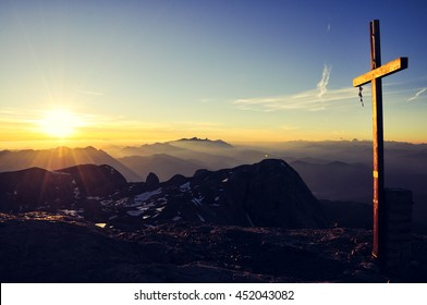 Sunrise seen from the summit of Hochkoenig mountain (Austria) at 2941m above sea level in the Berchtesgaden alps. Summit cross lit by rising sun. Dachstein group in background. Image cross processed.
