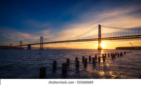 Sunrise at the SF-Oakland Bay Bridge with sun starburst, San Francisco, California