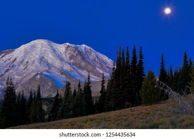 Sunrise shines on Mount Rainier with moon behind