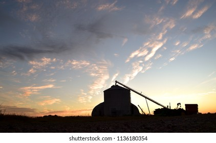 A sunrise shot of a farm silo, grain auger, and tractors, silhouetted against the morning sunrise.