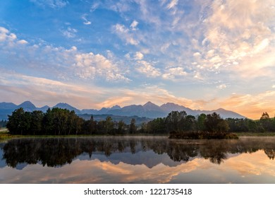 Sunrise shot of peaceful scene of beautiful autumn mountain landscape with lake, colorful trees and high peaks and golden sky in High Tatras, Slovakia.