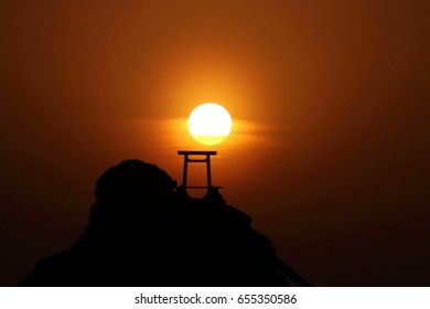 The sunrise and the silhouette of the husband-and-wife rock (Meotoiwa), in Ise, Mie, Japan.A torii (Red gate to a Japanese Shrine) and a Shimenawa (enclosing rope made by rice straw) on the rock.