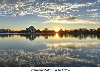 Sunrise skies at the National Mall in Washington, D.C. The Jefferson Memorial is illuminated on the horizon by the morning sunshine. Still waters of the Tidal Basin reflect wispy, cirrocumulus clouds.