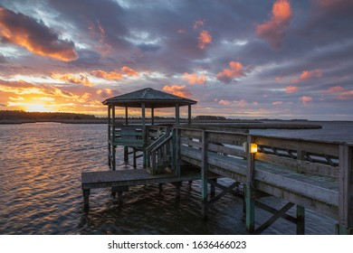 Sunrise sky and pink clouds over the gazebo on Roanoke Sound near the causeway at Whalebone Junction on the Outer Banks of North Carolina.