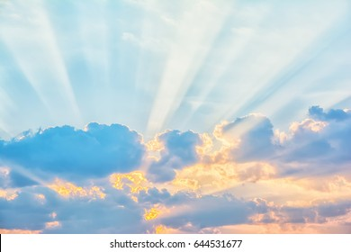 Sunrise sky with sun golden rays breaking through the clouds