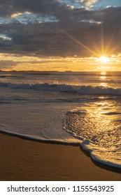 Sunrise with star burst at the beach, NSW, Australia