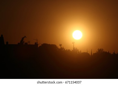Sunrise with sun and doves, Large solar disk on the horizon, intense orange, white and yellow colors, sunset, sun dawn,