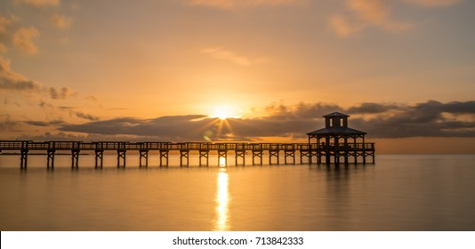 Sunrise or sunset above a boardwalk pier into the water. Warm reflections of the sun and pier on the water.