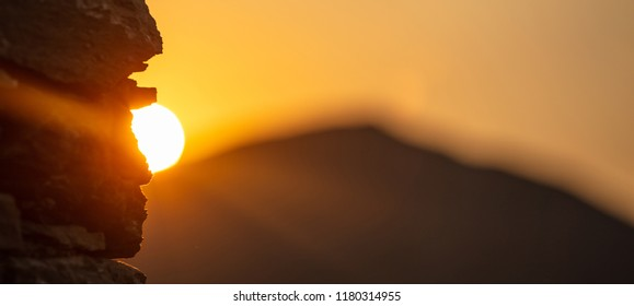 Sunrise, sunset over blur mountains silhouette. Sun behind rocks, colorful sky background, space, banner.