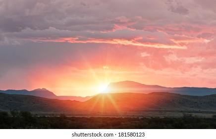 sunrise sunset over the distant mountain horizon