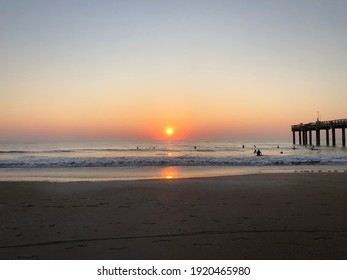 Sunrise or sunset over the ocean with surfers in the water next to a pier.