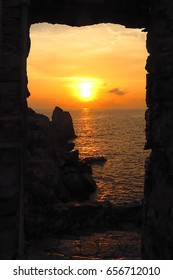 sunrise sunset over sea framed by stone window