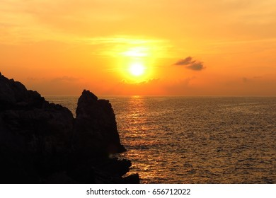 sunrise sunset over sea with rocky coast in foreground and copy space