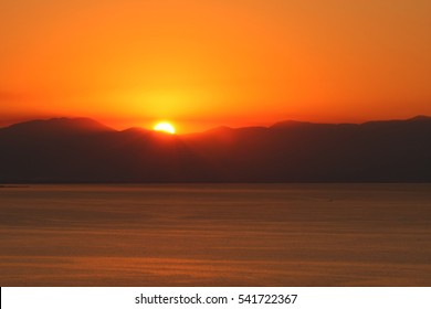 Sunrise or sunset at the sea behind the mountain