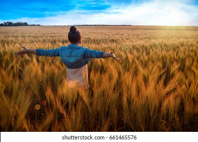 sunrise or sunset stylish adult woman standing back looking toward the horizon with widely placed hands on background of bright sky and Golden fields
