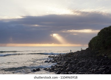 Sunrise with surfer on rocks at Burleigh Heads, Gold Coast, Australia