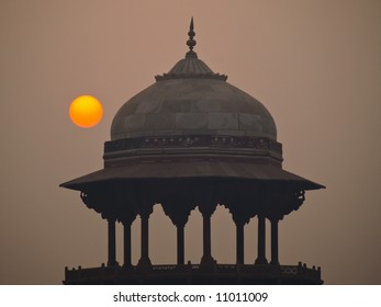 Sunrise through pollution with Mughal dome, Delhi, India