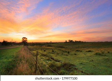 Sunrise throws a warm light over the countryside hills, paddocks and farm sheds.   Orchard Hills, Australia