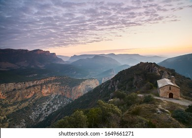 Sunrise from the top of a mountain with an ancient hermitage and views of other mountains