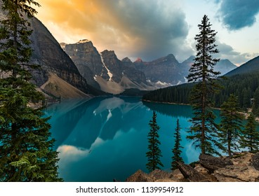 Sunrise with turquoise waters of the Moraine lake with sin lit rocky mountains in Banff National Park of Canada in Valley of the ten peaks.