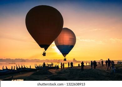 Sunrise at U Bein Bridge with boat and hot air balloon, Mandalay, Myanmar