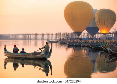 Sunrise at U Bein Bridge with boat and hot air balloon, Mandalay, Myanmar.