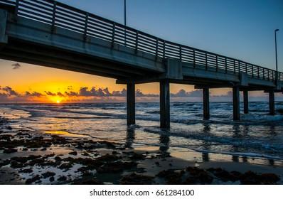 Sunrise Under Port Aransas Pier along Padre Island on a nice tranquil epic sunrise morning glow with sunbeams as sun rises over ocean / Sunrise under Port A Pier / Padre Island Corpus Christi Texas