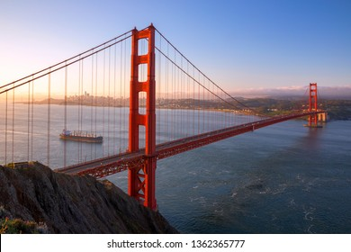 Sunrise view of the Golden Gate Bridge and fog from Battery Spencer with cargo ship, Golden Gate National Recreation Area, in San Francisco, California, USA.