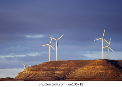 sunrise view of a group of windmills on a hill
