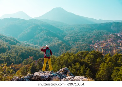 Sunrise View of Hiker on top of Rock overlooking layered Mountain Scenery rear view