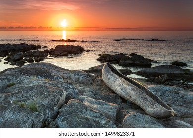 sunrise view at the Lake Malawi, waves rolling smoothly on the beach, wooden one tree boat in the foreground, Africa,