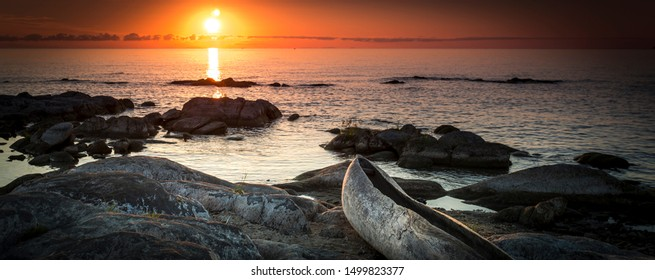 sunrise view at the Lake Malawi, waves rolling smoothly on the beach, wooden one tree boat in the foreground, Africa, Panorama