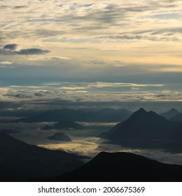 Sunrise view from Mount Brienzer Rothorn. Mount Stanserhorn and sea of fog on a cloudy summer morning.