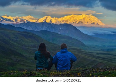Sunrise view of Mount Denali (mt Mckinley) peak with alpenglow during golden hour with two persons from Stony Dome overlook. Denali National Park and Preserve, Alaska, United States