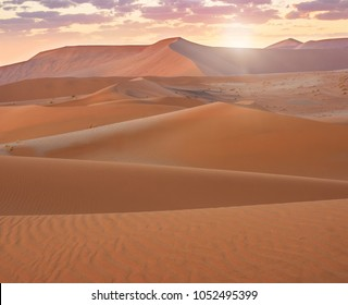 Sunrise view of the Namib Desert landscape, with the lines, curves, textures, and peaks of its large drifting sand dunes. Sossusvlei, Namibia.
