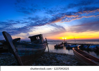 Sunrise view with stranded wooden boats at thousand island north jakarta