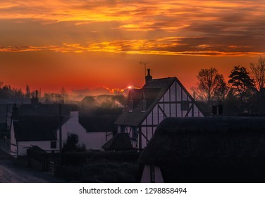 sunrise in the village of Monkton, Kent, UK. The sun is just appearing behind a cloud producing a rim light and misty haze enhanced by smoke from a chimney. The houses traditional