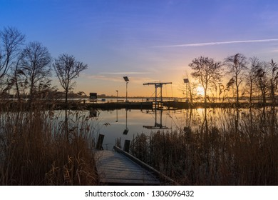 Sunrise in winter above al lake. Dike with bridge. Old crooked jetty and reeds in the foreground.